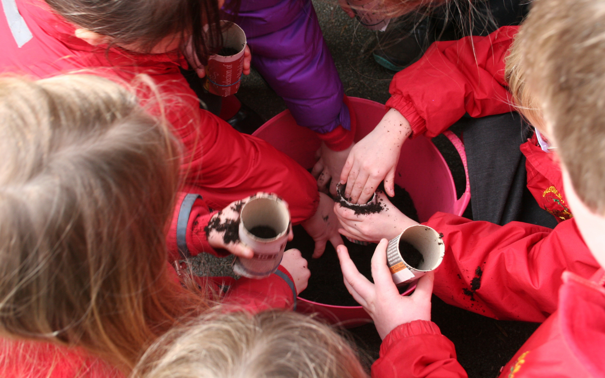 aerial shot of children filling pots with compost