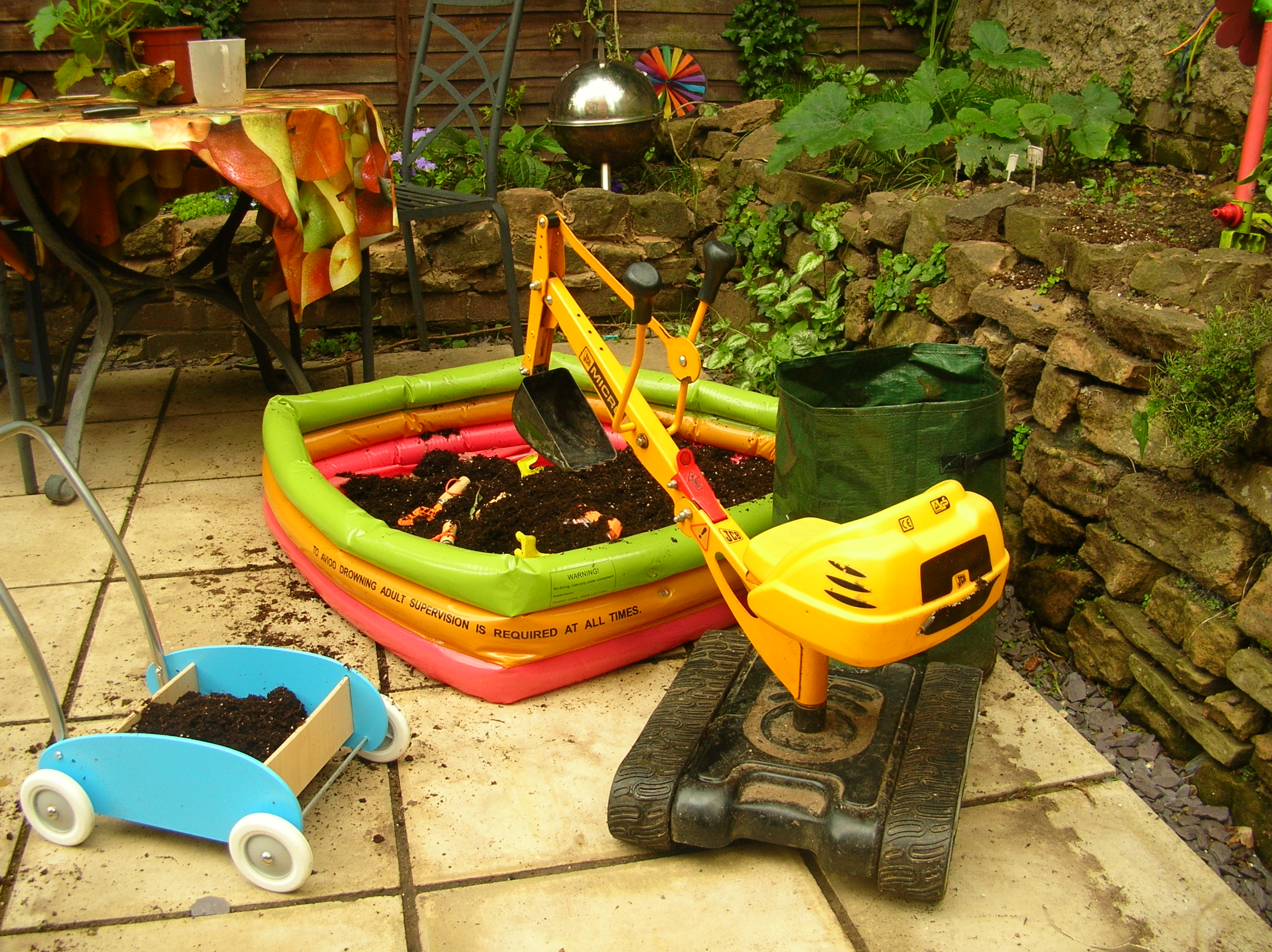 paddling pool and toy diggers being used to harvest potatoes